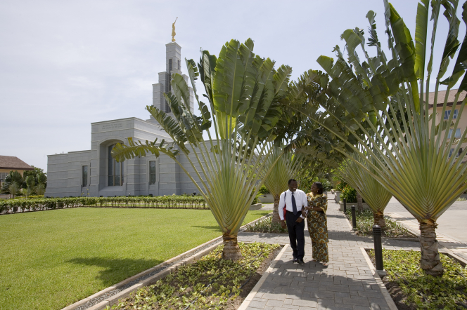 A couple walking with clasped arms down a sidewalk with the Accra Ghana Temple in the background.