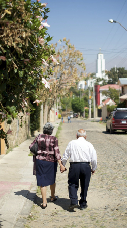 An elderly man and woman holding hands as they walk down a road to the Cochabamba Bolivia Temple in the distance.