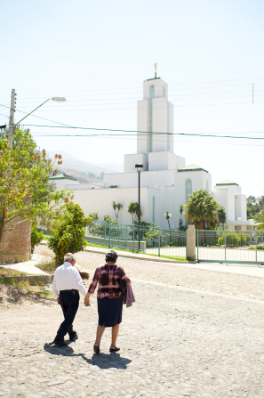 An elderly couple holding hands and walking across a street in front of the Cochabamba Bolivia Temple.