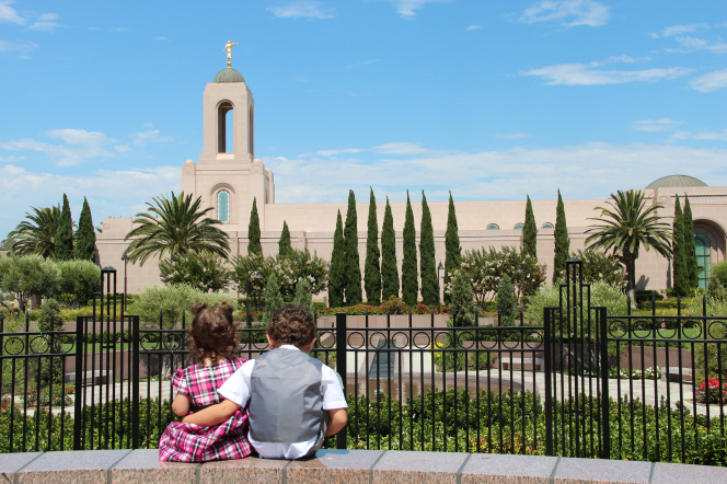 A little boy with brown curly hair putting his arm around his sister as they sit and look at the Newport Beach California Temple.