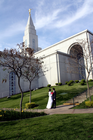 A bride holding a bouquet of red flowers and standing beside the groom as they look up at the Campinas Brazil Temple.