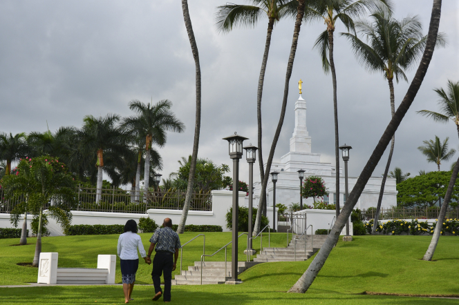 A woman in a white blouse and blue skirt holding hands with her husband in a blue shirt and pants as they walk on the Kona Hawaii Temple grounds.