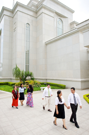 A young couple holding hands and walking outside the Guayaquil Ecuador Temple with other adults walking behind them.