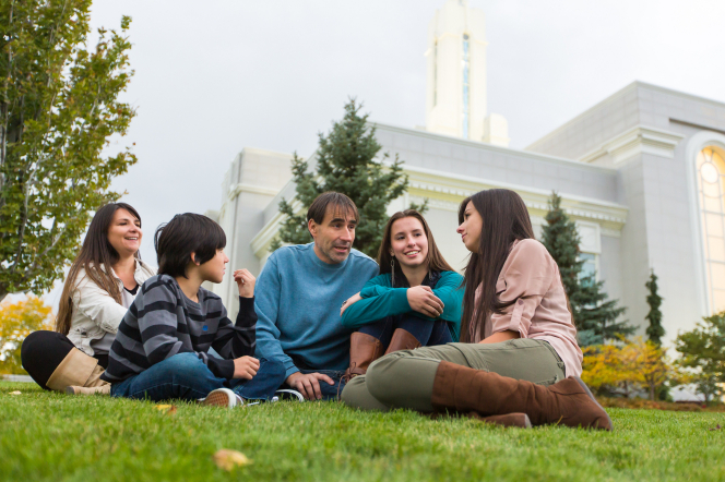A father, mother, two daughters, and a son sit on the grass near trees and talk outside the Mount Timpanogos Utah Temple.