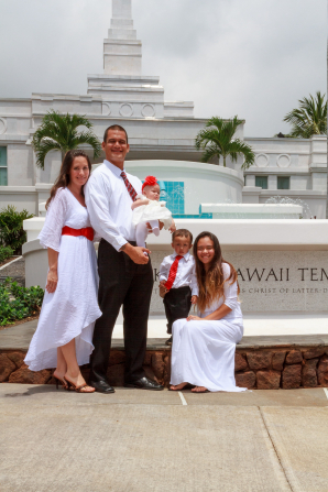 A mother and two daughters in white dresses with a father and son in white shirts and red ties standing outside the Kona Hawaii Temple after being sealed.
