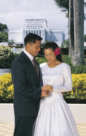 A bride with a red flower in her hair, standing and holding hands with the groom outside a temple in Hawaii.