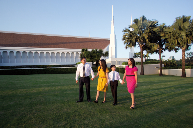 A father, daughter, son, and mother walking in a row and holding hands outside the Manila Philippines Temple.