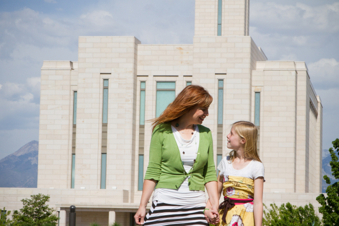 A mother in a white shirt, green cardigan, and striped skirt holding hands and walking with her daughter in a yellow dress outside a temple.