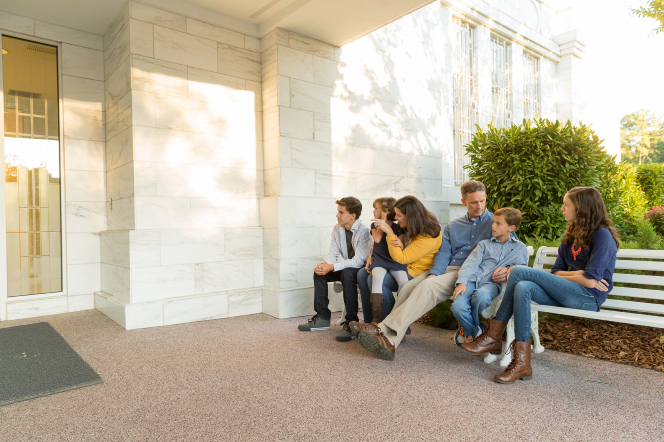 A mother, father, two sons, and two daughters sitting on white benches outside the doors of the Raleigh North Carolina Temple.
