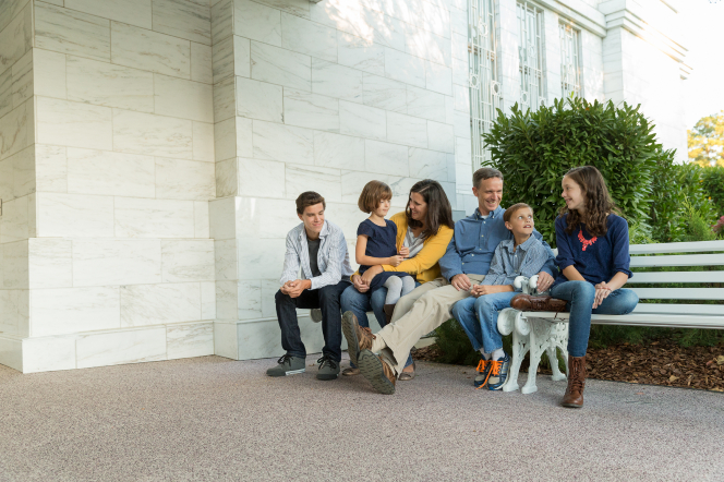 A father, mother, two sons, and two daughters talking and sitting on white benches outside the Raleigh North Carolina Temple.