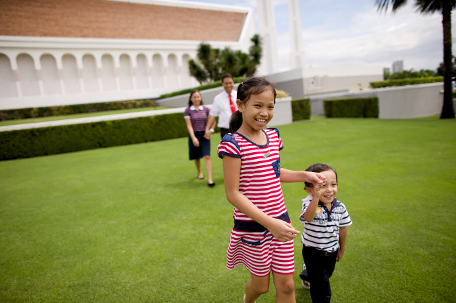 A girl walking and holding hands with her younger brother as their parents walk behind them, holding hands, outside the Manila Philippines Temple.