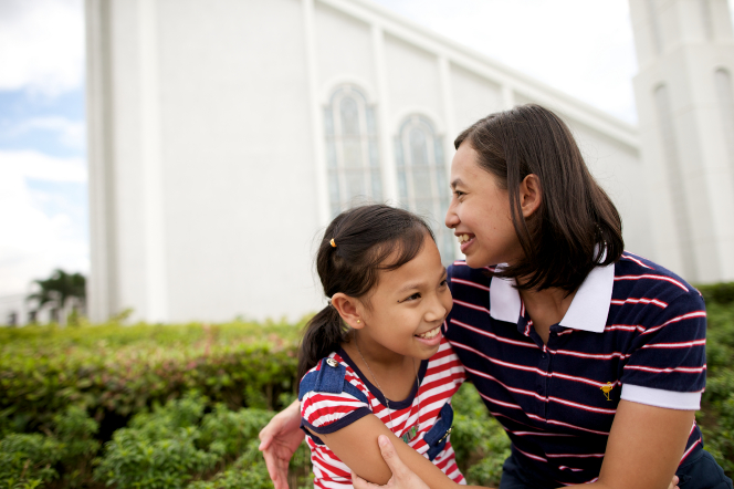 A mother smiling and hugging her young daughter while sitting outside of the Manila Philippines Temple.
