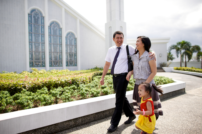 A man puts his arm around the shoulders of his wife as they walk beside their young daughter on the sidewalk by the Manila Philippines Temple.