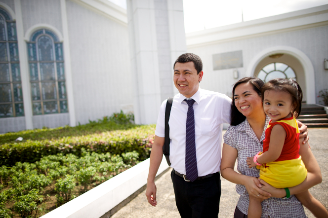 A man putting an arm around his wife's shoulders as she carries their young daughter outside the Manila Philippines Temple.