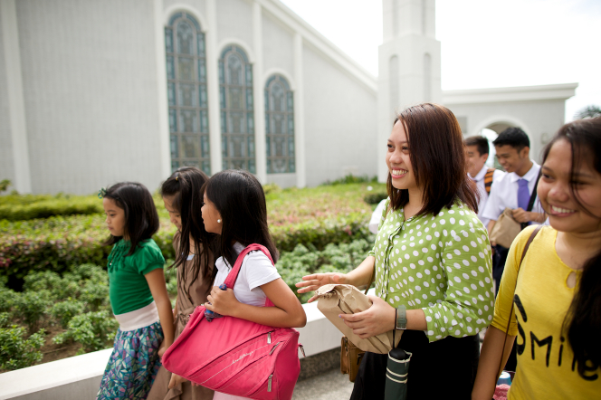 A group of young women and young men and their leader smiling while walking outside the Manila Philippines Temple.