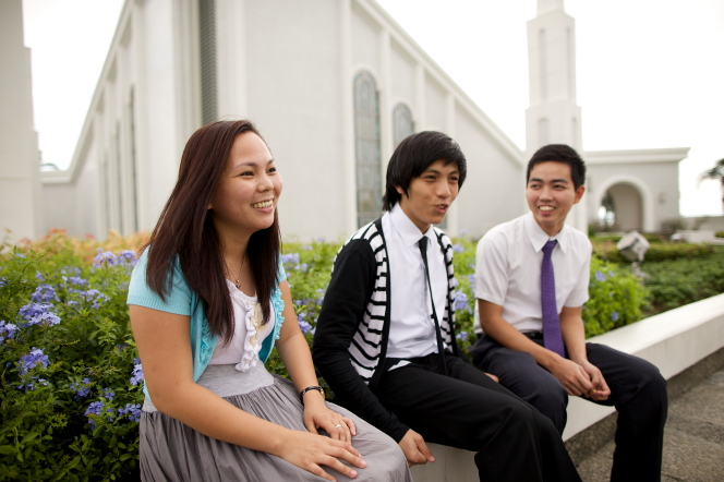 A young woman with brown hair, a white shirt, a blue cardigan, and a gray skirt sitting by two young men outside the Manila Philippines Temple.