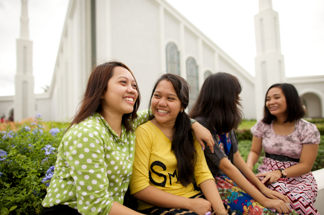 A young woman putting her arm around another young woman's shoulders, with two other women sitting nearby outside the Manila Philippines Temple.