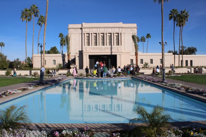 A group of people waiting for a bride and groom to come out of the Mesa Arizona Temple doors, with a clear blue sky overhead.