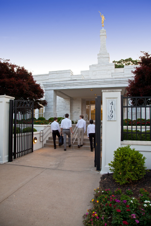 Four young men in white shirts walking up stairs leading to the Memphis Tennessee Temple.