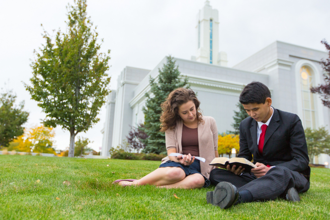 A young man and young woman sitting on the grass near trees and reading from scriptures outside the Mount Timpanogos Utah Temple.