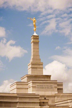 A close-up image of the spire and angel Moroni statue on top of the Aba Nigeria Temple on a sunny day.