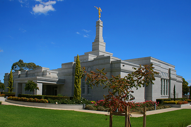 An angled view of the Adelaide Australia Temple in the daytime, with a bright blue sky overhead.
