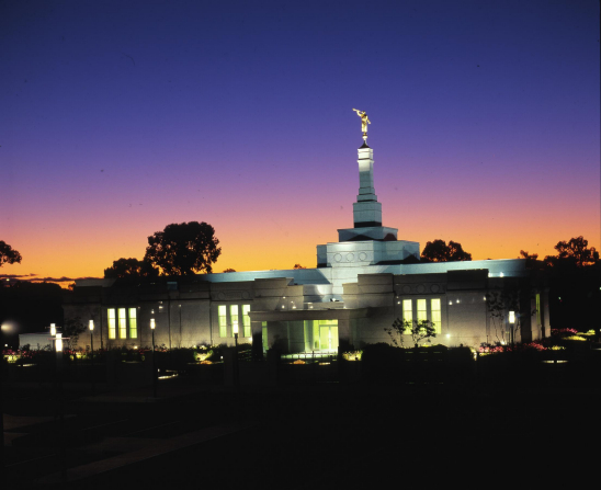 The Adelaide Australia Temple lit up at night in front of a backdrop of a deep purple sky.