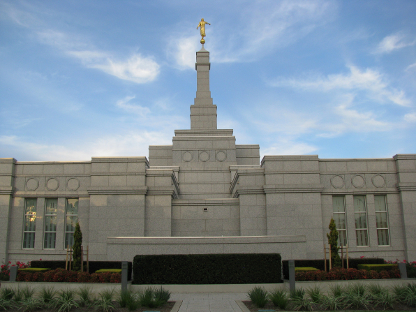 The back of the Adelaide Australia Temple, with manicured bushes and stone pathways.