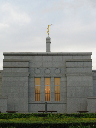 A side view of the exterior of the Adelaide Australia Temple, with the spire and angel Moroni in view.