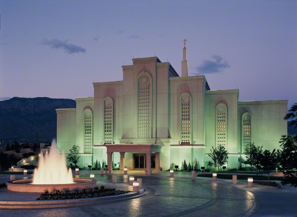 The Albuquerque New Mexico Temple in the late evening, with the lights on the temple grounds illuminating the temple's exterior.