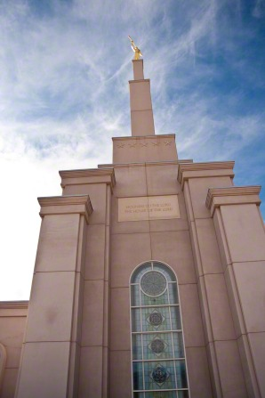 A view of the spire on the Albuquerque New Mexico Temple as seen from below, looking toward a blue sky with clouds.