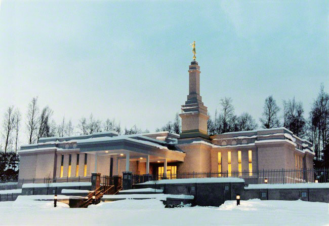 A view of the front of the Anchorage Alaska Temple on a snowy evening, with the lights glowing inside the windows.