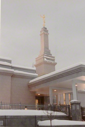 The spire and front entrance of the Anchorage Alaska Temple on a snowy day.