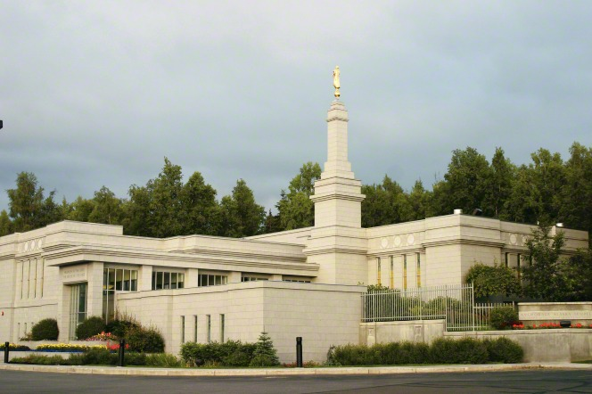 A view of the entire Anchorage Alaska Temple on a sunny summer day, with green lawns and plants on the grounds.