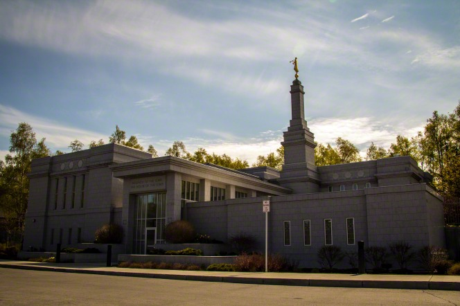 """A daytime view of the Anchorage Alaska Temple, with the words """"Holiness to the Lord: The House of the Lord"""" in view above one of the doors."""