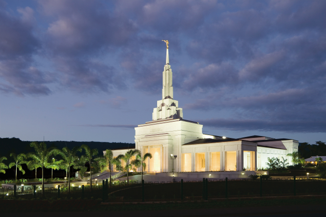 The Apia Samoa Temple lit up in the late evening, with a row of palm trees leading up to the front door.