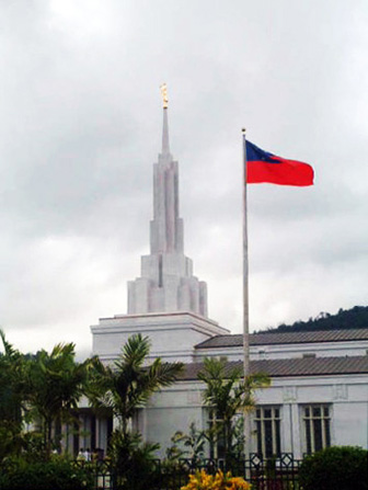 The Samoan flag on the grounds of the Apia Samoa Temple, with the temple's spire and the angel Moroni seen in the background.
