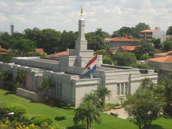 The Asunción Paraguay Temple seen among the surrounding community, with the Paraguayan flag in the foreground.