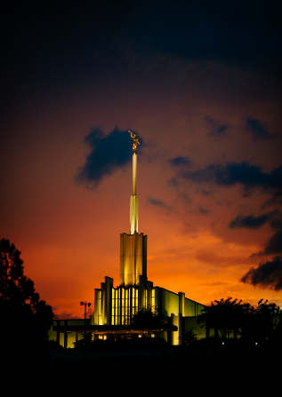 The front of the Atlanta Georgia Temple lit up during sunset, with a deep orange sky in the background.