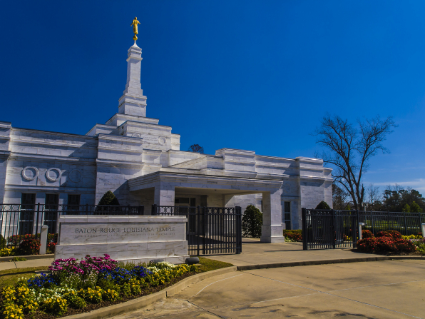 A daytime photograph of the front of the Baton Rouge Louisiana Temple, showing the temple's sign and the flower beds in full bloom.