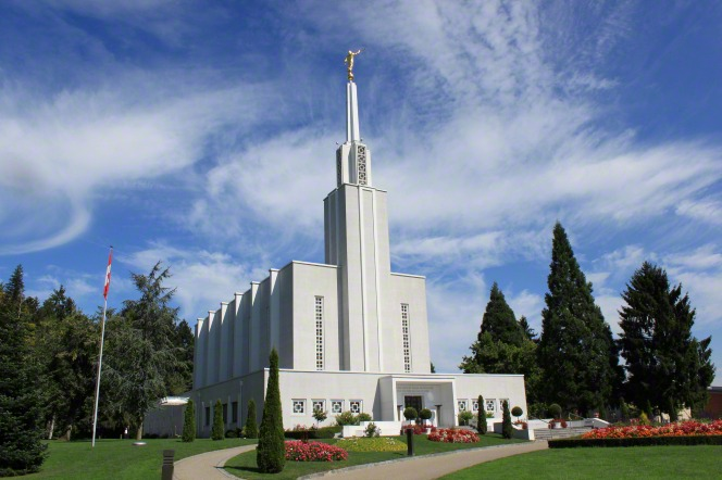 A view from the front of the Bern Switzerland Temple, with green trees on the grounds and blue sky and white clouds in the background.