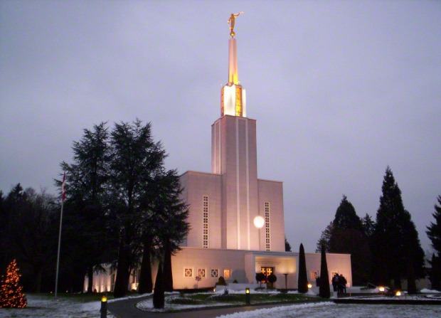 The Bern Switzerland Temple on a snowy evening, with a tree on the grounds strung with lit Christmas lights.
