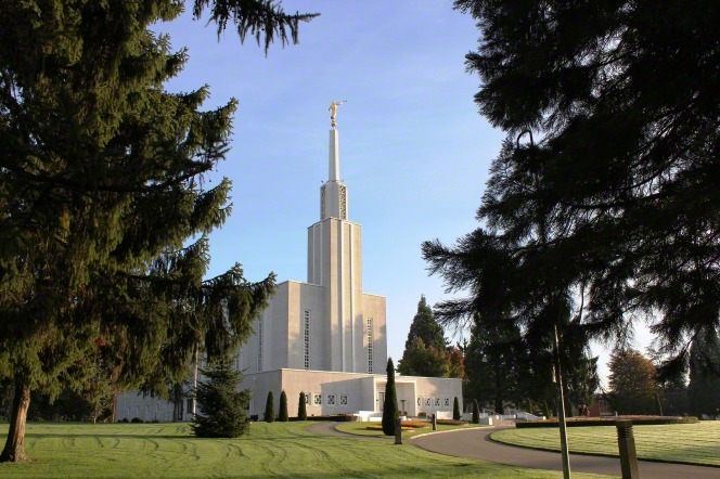 The Bern Switzerland Temple, seen between two pine trees on the temple's grounds.