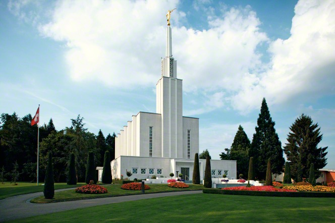 A daytime view of the front of the Bern Switzerland Temple, with the Swiss flag flying on the grounds.