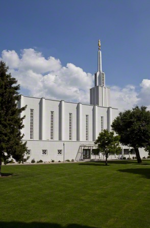 A view of the side of the Bern Switzerland Temple, with a blue sky and large white clouds in the background.