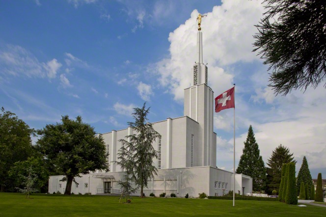 The side of the Bern Switzerland Temple, with the Swiss flag flying in the foreground.