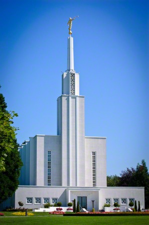 The front of the Bern Switzerland Temple on a sunny day, with green lawns and trees and blooming flowers in the flower beds.