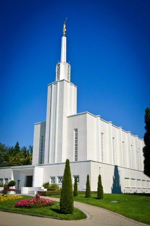 The front of the Bern Switzerland Temple on a sunny day, with well-manicured trees, bushes, and lawns.