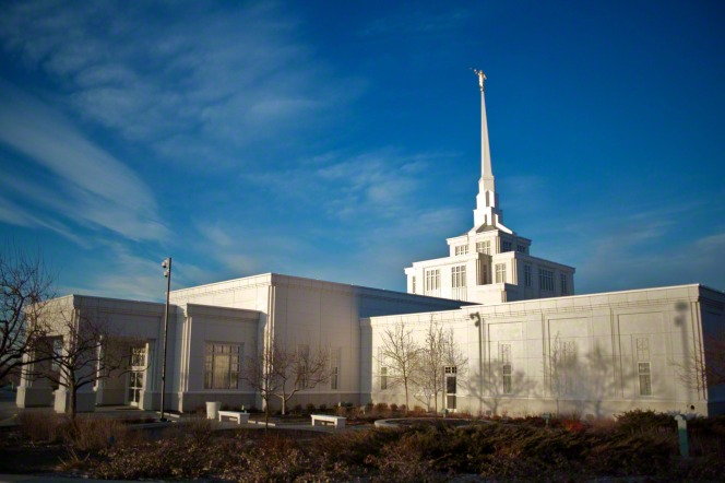 A side view of the Billings Montana Temple in the wintertime, with bare trees on the grounds.