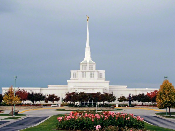 A view of the front of the Billings Montana Temple on a fall day, with flowers in the foreground.